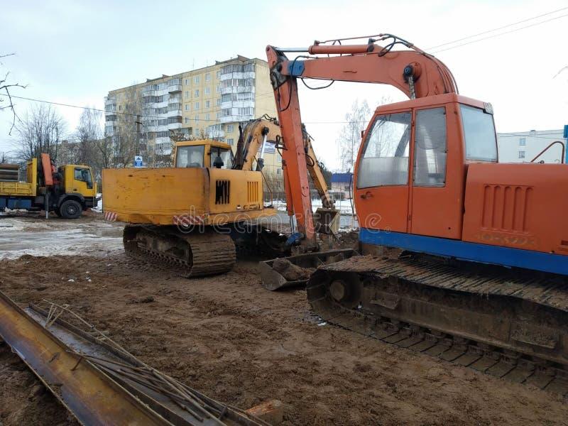 Reparaturbauarbeiten, der Hydraulikbagger auf Gleiskettenfahrzeug zum Kurs der orange und gelben Farbe, Bodenbewegung in der Stad stockbilder