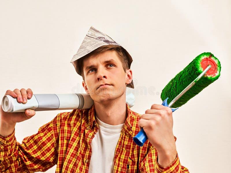 Repare al hombre casero que sostiene el rodillo de pintura para el papel pintado fotografía de archivo