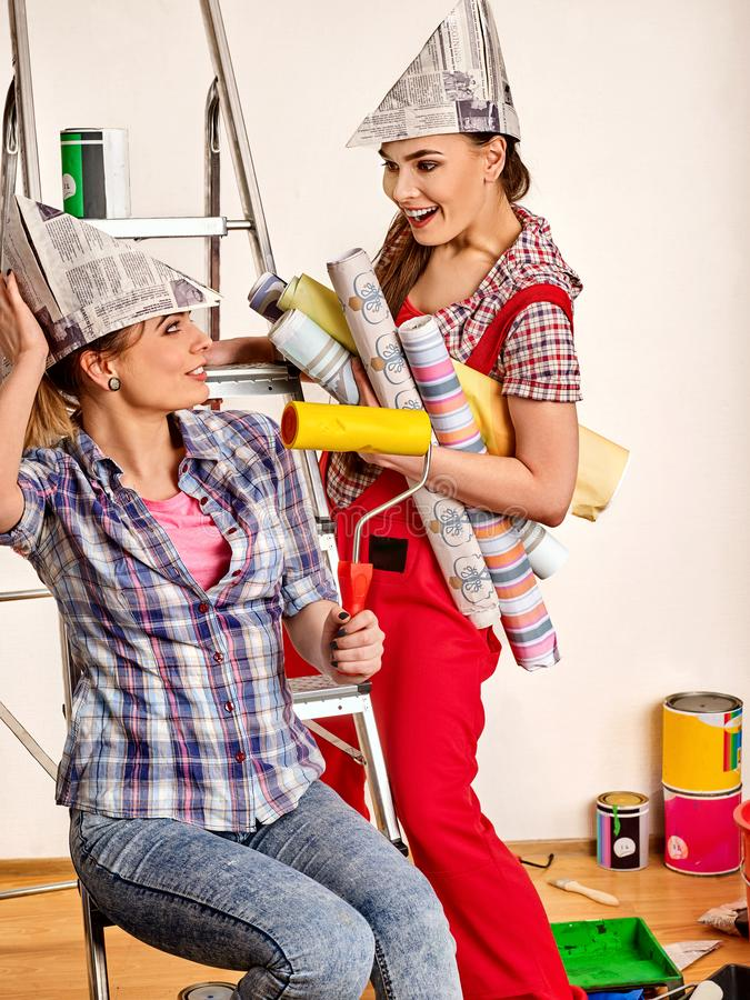 Repare as mulheres home que guardam o rolo das ferramentas da pintura para o papel de parede foto de stock