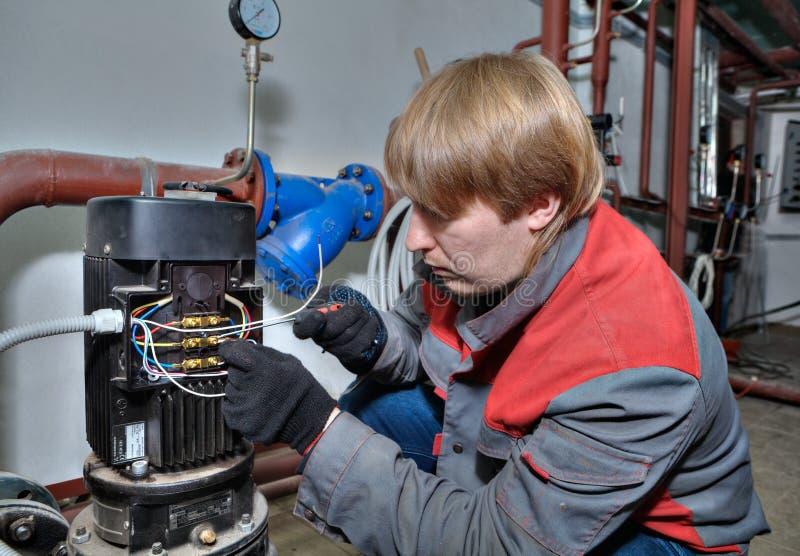 Repare el sistema de calefacción de la bomba, mecánico conecta los alambres con eléctrico imágenes de archivo libres de regalías