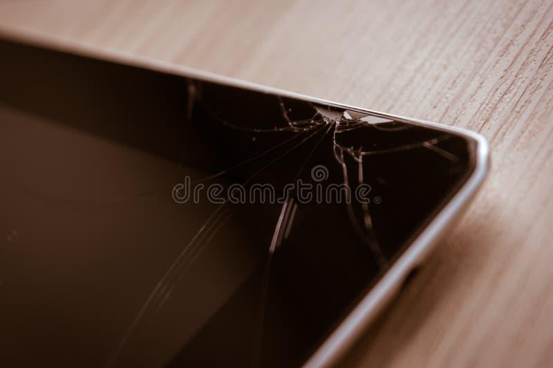 Repare la tableta del ordenador con la pantalla táctil quebrada en el escritorio de madera fotografía de archivo libre de regalías