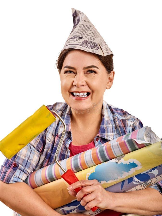Repare a mulher home que guarda o rolo de pintura para o papel de parede foto de stock