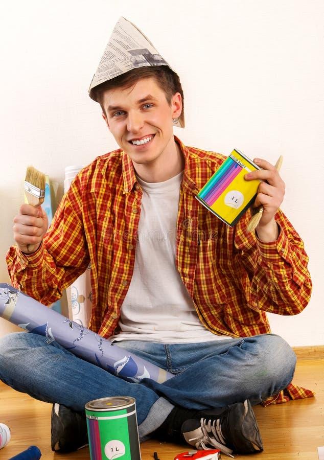 Repare o homem home que guarda o rolo de pintura para o papel de parede imagem de stock royalty free