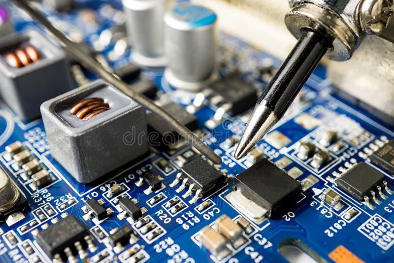 Repare o microchip com ferro e lata de solda imagens de stock royalty free