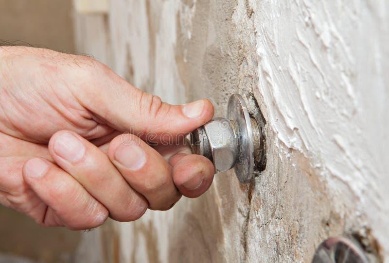 Repare o torneira da montagem da parede, voltas do encanador da mão do close-up excêntricas fotos de stock royalty free