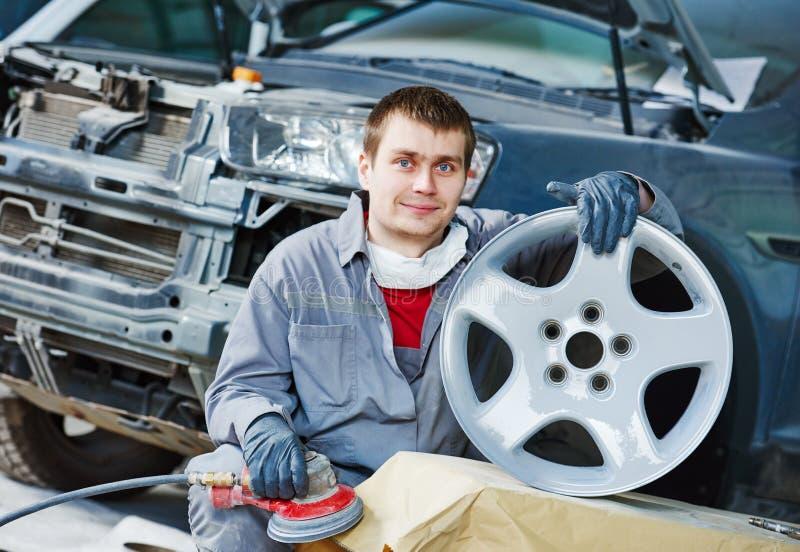 Repare o trabalhador do mecânico com a borda do disco da roda de carro da liga clara imagens de stock royalty free