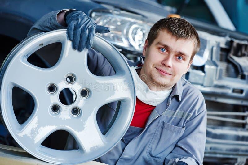 Repare o trabalhador do mecânico com a borda do disco da roda de carro da liga clara imagens de stock