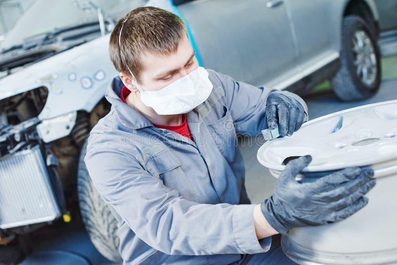 Repare o trabalhador do mecânico com a borda do disco da roda de carro da liga clara fotos de stock