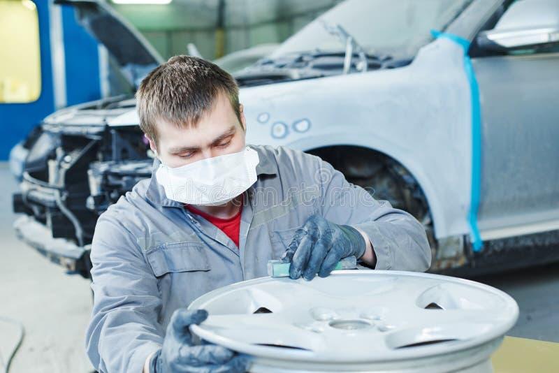 Repare o trabalhador do mecânico com a borda do disco da roda de carro da liga clara imagem de stock royalty free