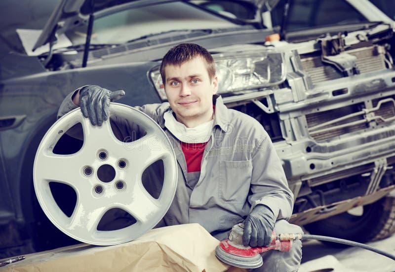 Repare o trabalhador do mecânico com a borda do disco da roda de carro da liga clara fotografia de stock