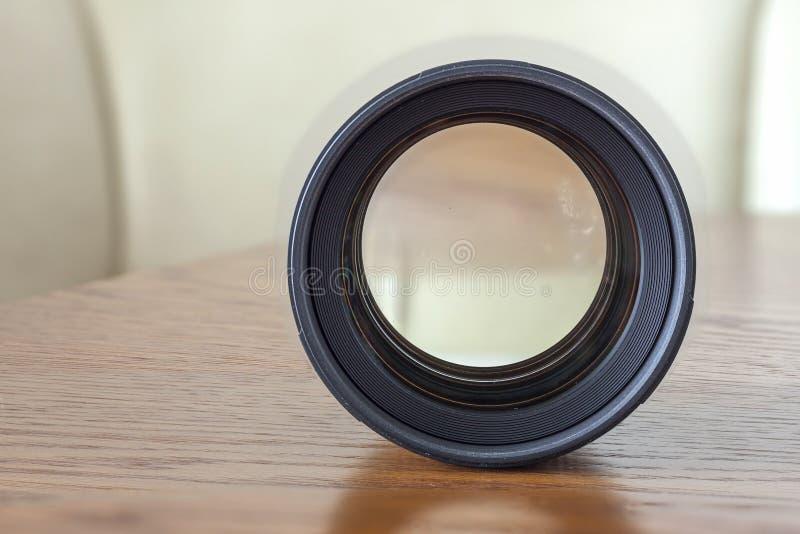 Reparieren Sie Linse einer SLR-Kameranahaufnahme mit einer Reflexion auf einem hölzernen Hintergrund lizenzfreies stockbild