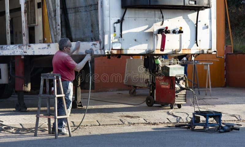 Reparieren Sie schweres Fahrzeug des Anhängers, Reinigungsrost, Gips, Farbe stockbild