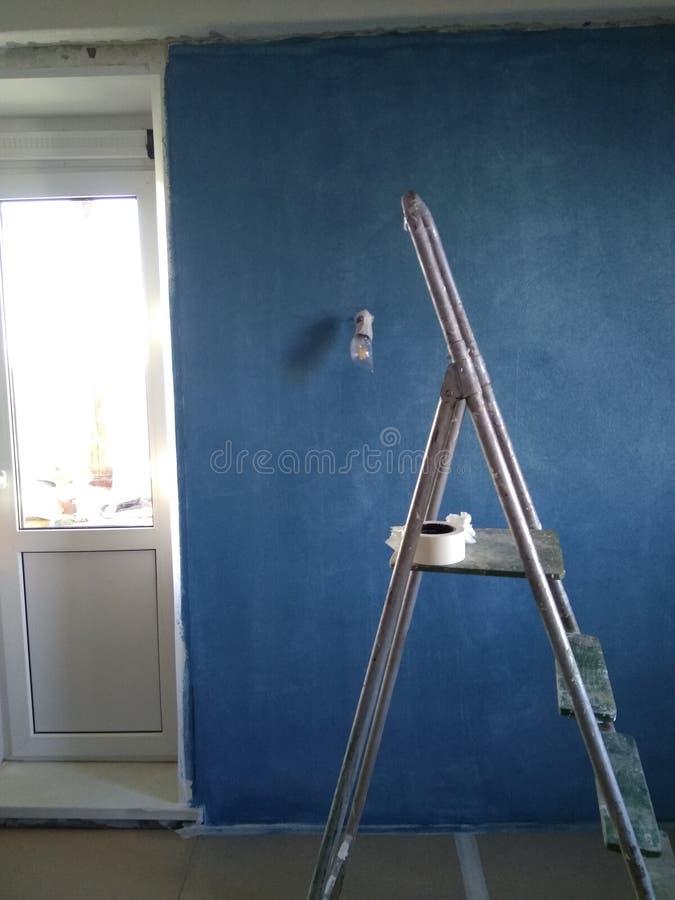 Reparo com o papel de parede para a pintura, a pintura azul e a escada imagem de stock royalty free