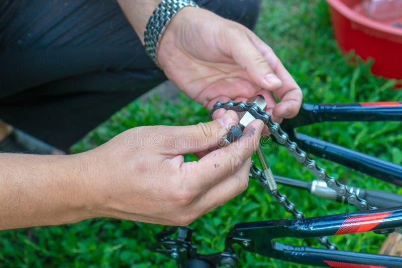 Reparo da bicicleta Homem novo que repara a bicicleta na floresta imagem de stock royalty free