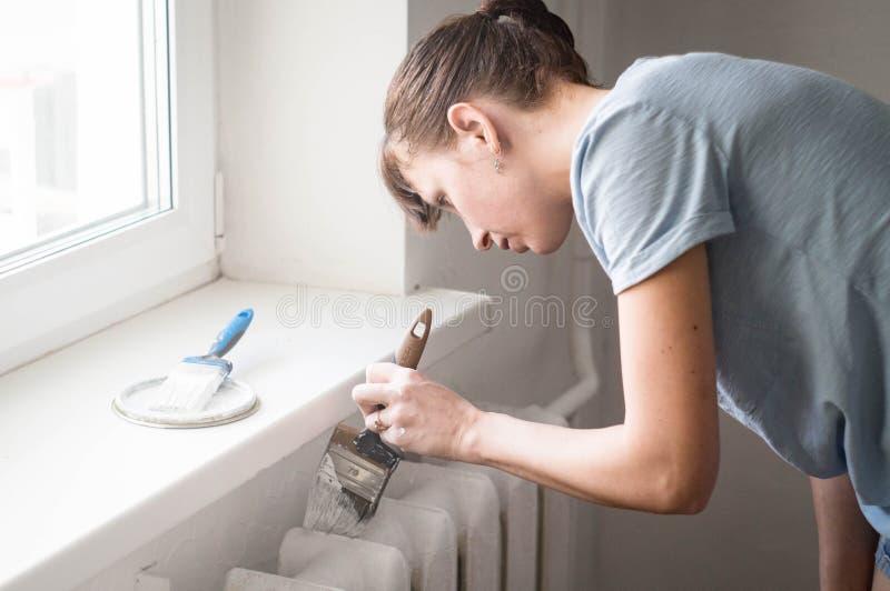 Reparo da casa: a menina ruivo pinta delicadamente o radiador com uma escova no branco Conceito: atenção, precisão fotos de stock royalty free