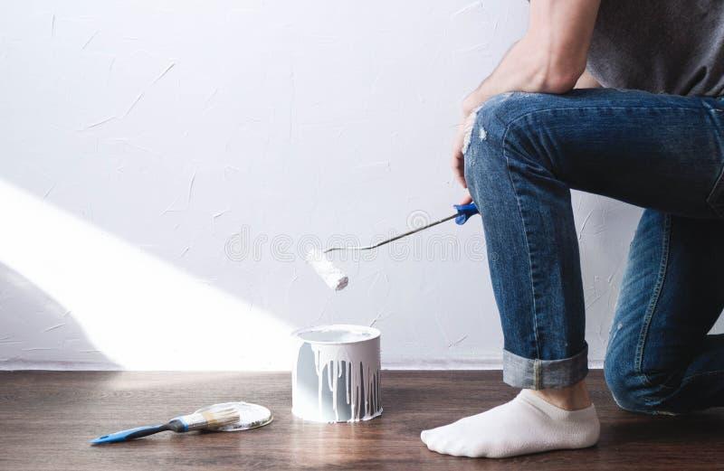 Reparo da casa: o homem está indo pintar a parede com um rolo no branco Esfrega em um frasco com pintura branca fotografia de stock