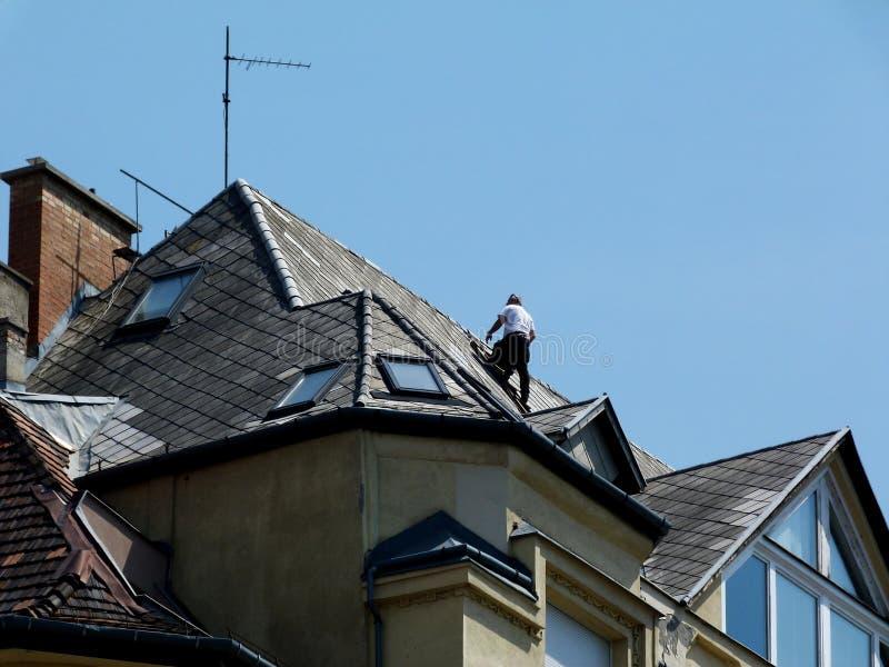 Reparo da chaminé no telhado alto da construção velha clássica imagem de stock