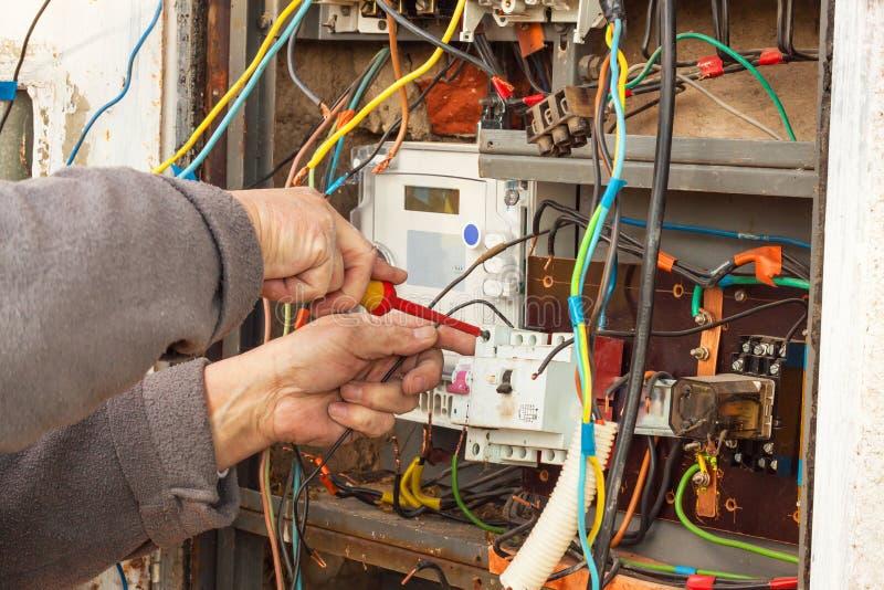 Reparo da distribuição da eletricidade em uma casa velha O homem repara o painel de comando fotografia de stock