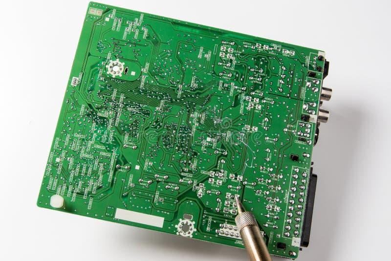 Reparo da placa de sistema eletrônica com ferro de solda fotografia de stock