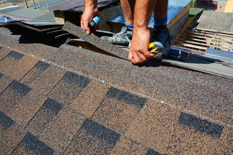 Reparo de um telhado das telhas O feltro ou o betume do telhado do corte do Roofer durante waterproofing trabalham Telhas do telh imagem de stock royalty free