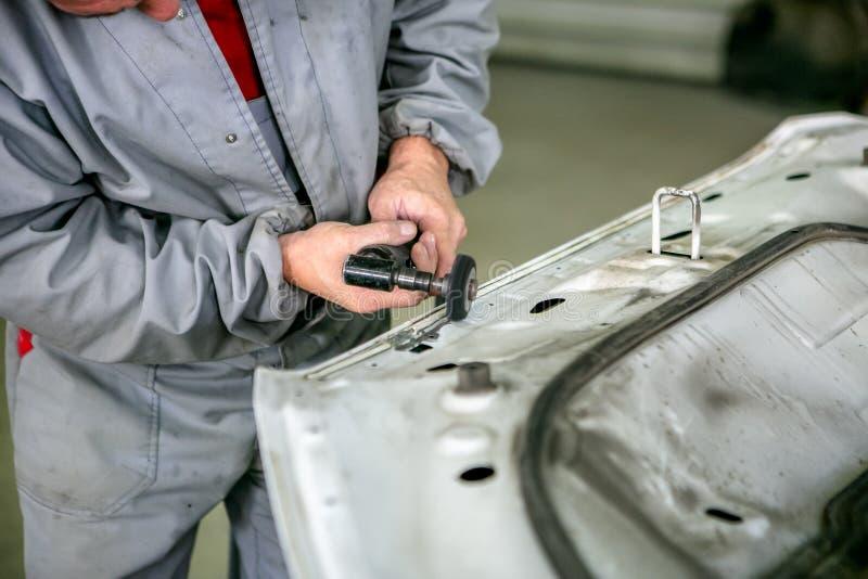Reparo do carro no serviço do carro Detalhe do carro das moagens do serralheiro, close-up das mãos imagem de stock