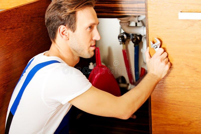 Reparo do homem novo algo armário de cozinha do interior sob o dissipador imagens de stock