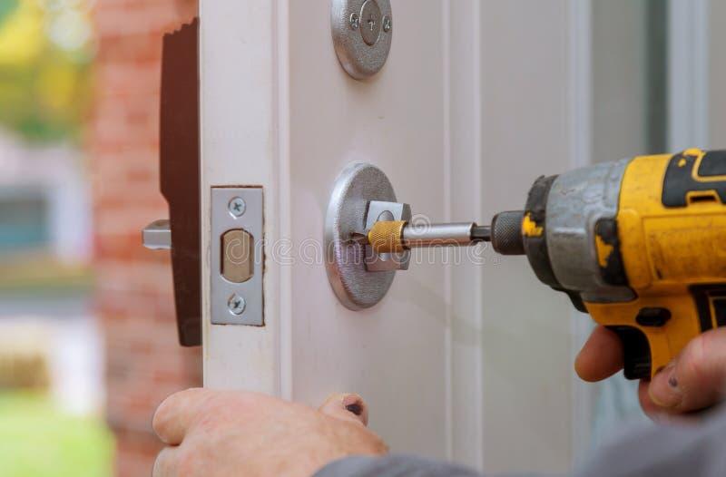reparo do trabalhador manual a fechadura da porta no worker& x27; mãos de s que instalam o cacifo novo da porta foto de stock