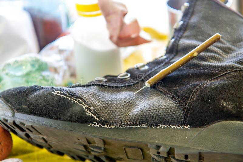 Reparo dos calçados para a sobrevivência nas condições de uma caminhada fotos de stock