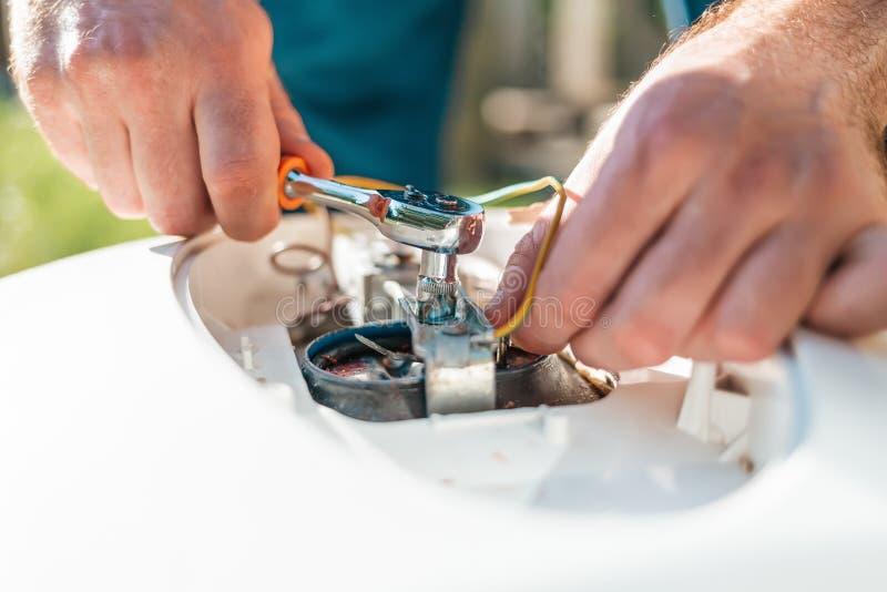Reparo e manutenção do aquecedor de água O detalhe da fixação do homem da caldeira As mãos e os dedos fecham-se acima imagem de stock