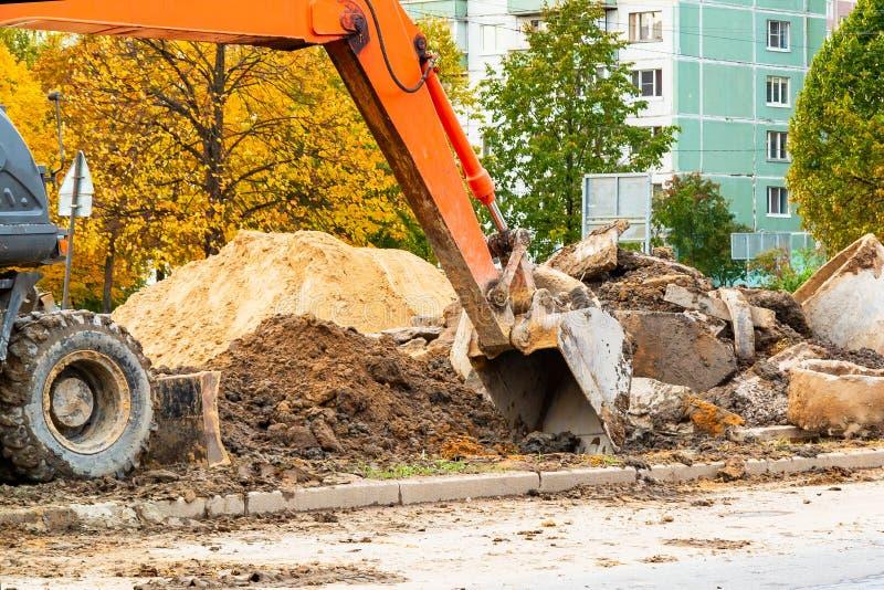 Reparo em uma rua da cidade, ancinhos na terra, close-up da estrada de uma cubeta da máquina escavadora imagem de stock royalty free