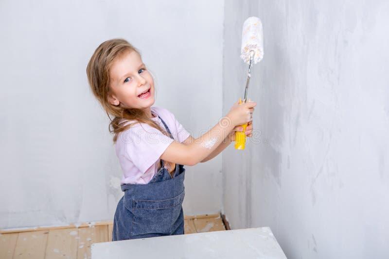 Reparo no apartamento A mãe e a filha felizes da família nos aventais pintam a parede com pintura branca menina que guarda o rolo imagem de stock royalty free