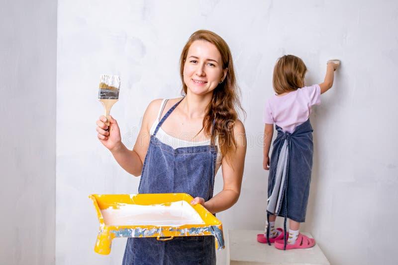 Reparo no apartamento A mãe e a filha felizes da família nos aventais pintam a parede com pintura branca a filha pinta a parede fotografia de stock
