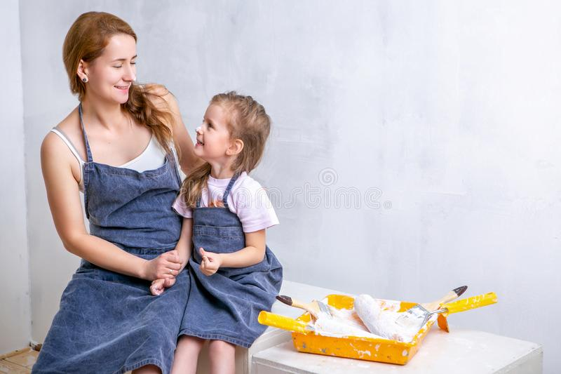 Reparo no apartamento A mãe e a filha felizes da família nos aventais pintam a parede com pintura branca A mãe e a filha sentam o imagem de stock