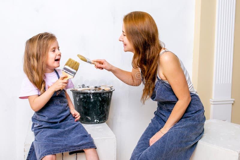 Reparo no apartamento A mãe e a filha felizes da família nos aventais prepararam-se para pintar a parede com pintura branca Sente foto de stock