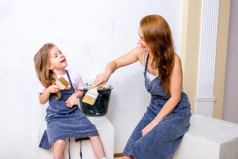 Reparo no apartamento A mãe e a filha felizes da família nos aventais prepararam-se para pintar a parede com pintura branca Sente imagens de stock