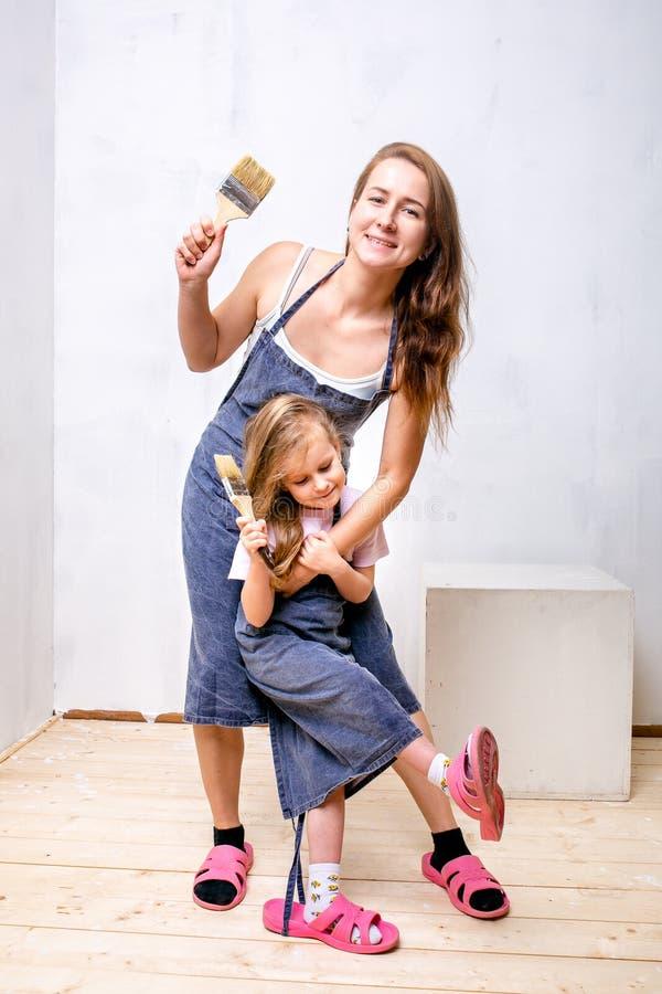 Reparo no apartamento A mãe e a filha felizes da família nos aventais prepararam-se para pintar a parede com pintura branca Supor imagens de stock royalty free