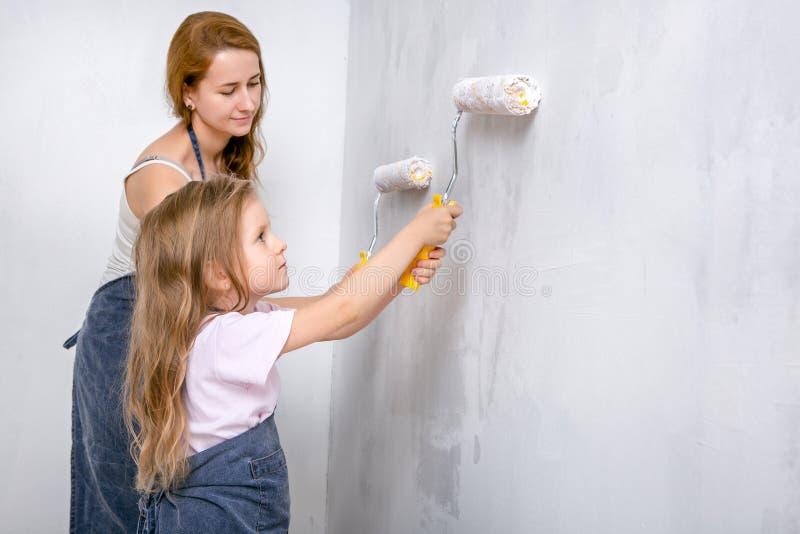 Reparo no apartamento A mãe feliz da família e a filha pequena em aventais azuis pintam a parede com pintura branca fotos de stock royalty free