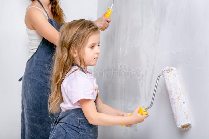 Reparo no apartamento A mãe feliz da família e a filha pequena em aventais azuis pintam a parede com pintura branca Pinturas da f fotos de stock