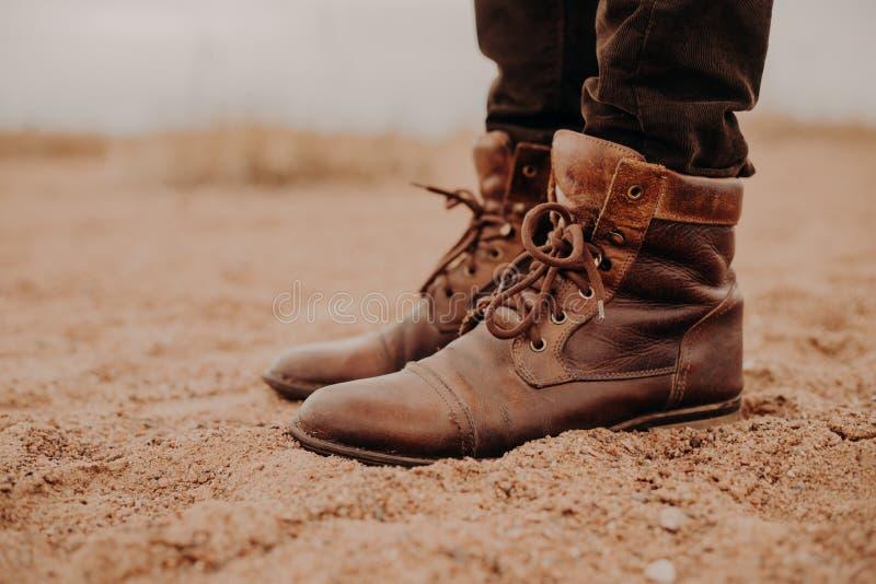 Reparo requring dos calçados O homem veste sapatas velhas com laços, suportes na terra, levanta exterior Tiro colhido Carregador  imagem de stock