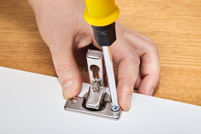 Reparos do reparador nas dobradiças de porta da mobília imagem de stock royalty free