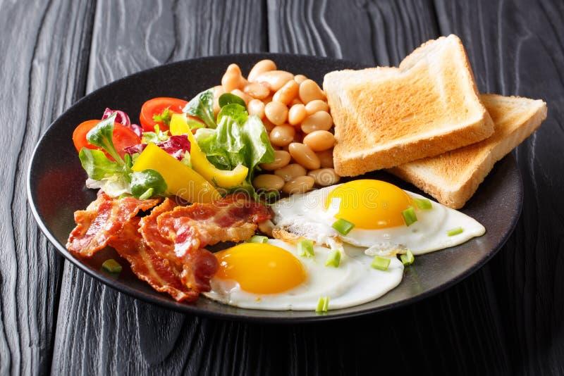 Repas délicieux et chaleureux : deux oeufs au plat avec le lard, haricots, TOA photographie stock