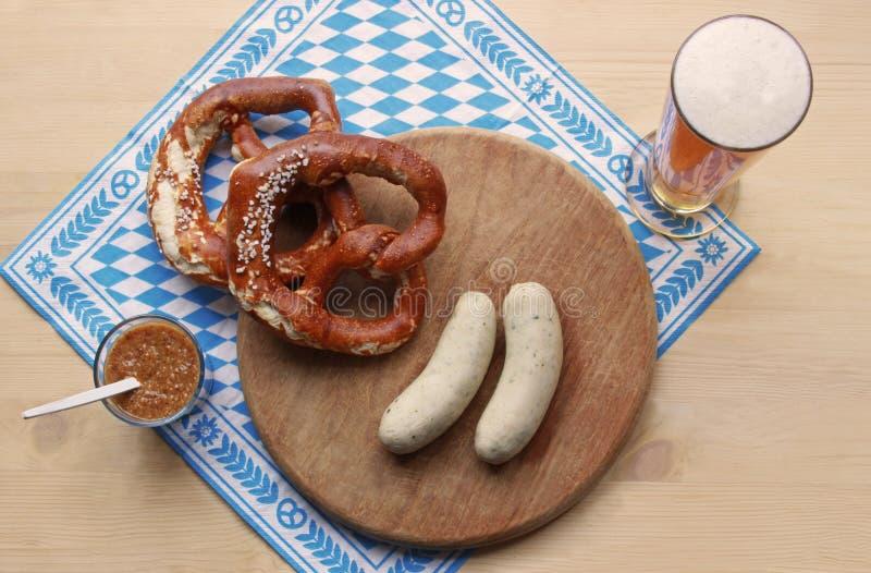 Repas d'Oktoberfest avec des bretzels, des saucisses de Munich et le blé blancs images stock