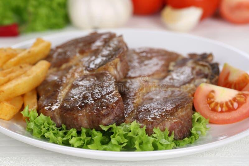 Repas de biftecks de côtelettes de porc avec des fritures, des légumes et la laitue sur le pla photographie stock