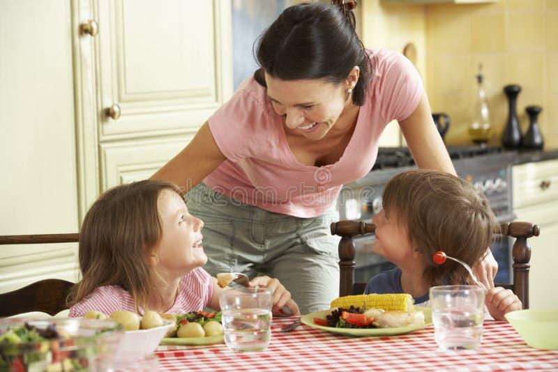 Repas de portion de mère aux enfants dans la cuisine photos stock