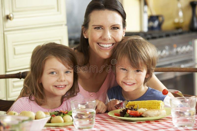 Repas de portion de mère aux enfants dans la cuisine images stock