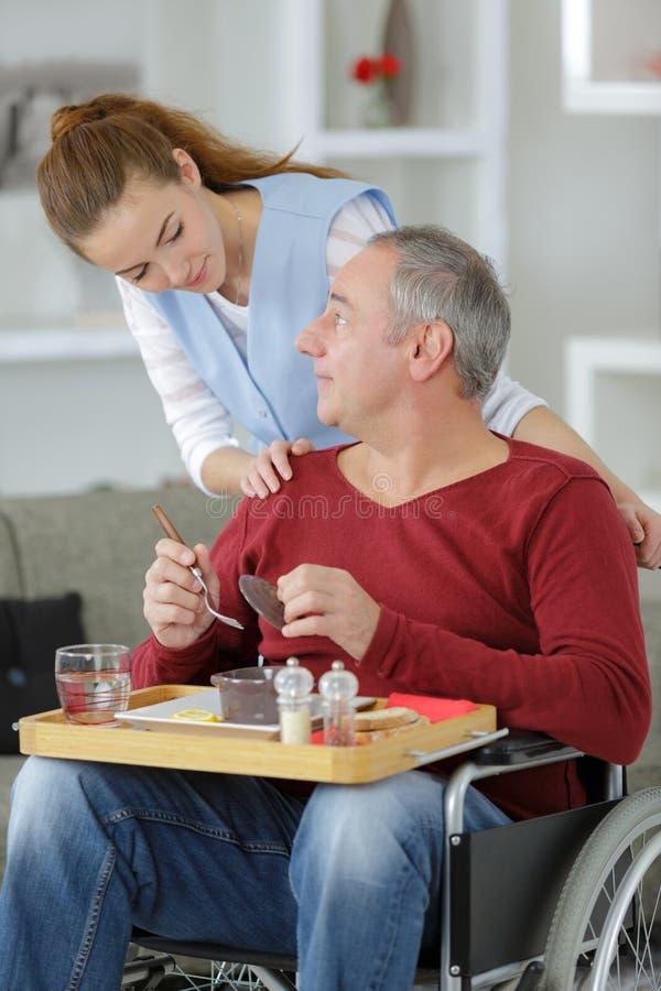 Repas de portion de soignant à l'homme dans le fauteuil roulant à la maison photo libre de droits