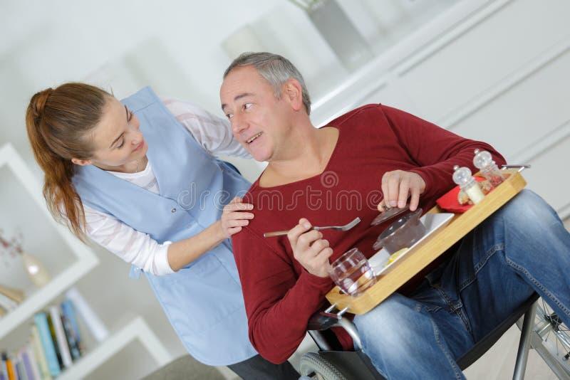 Repas de portion de soignant à l'homme dans le fauteuil roulant à la maison photographie stock libre de droits