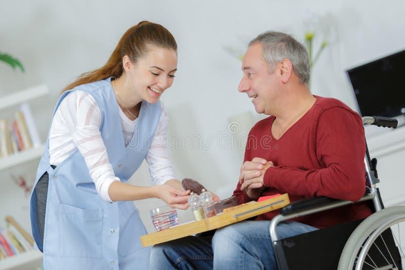 Repas de portion de soignant à l'homme dans le fauteuil roulant à la maison photographie stock