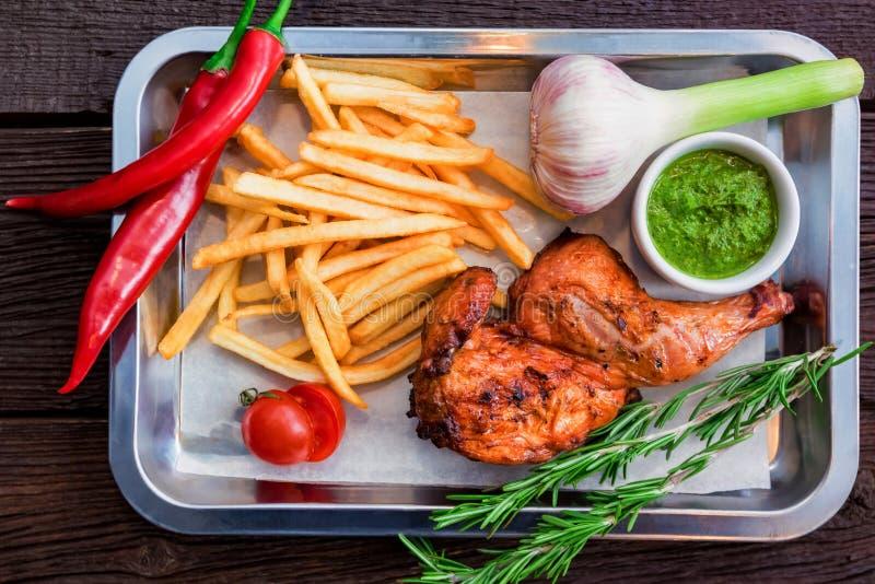 Repas de vue supérieure avec la cuisse de poulet, les pommes frites, le poivre de piment et l'ail image stock