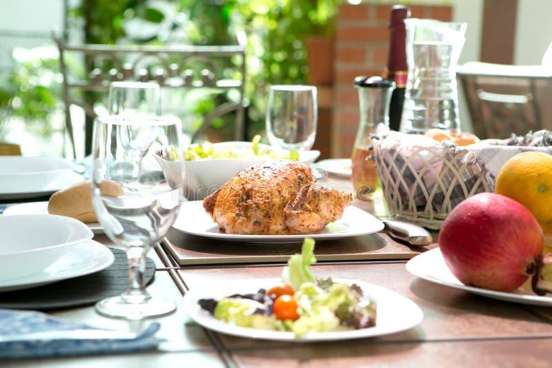 Repas dinant extérieur complet avec le poulet rôti, la salade, les petits pains de pain, le vin et le fruit en été photographie stock libre de droits